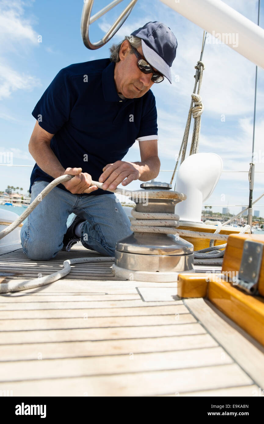Middle-aged man winching rope on yacht - Stock Image