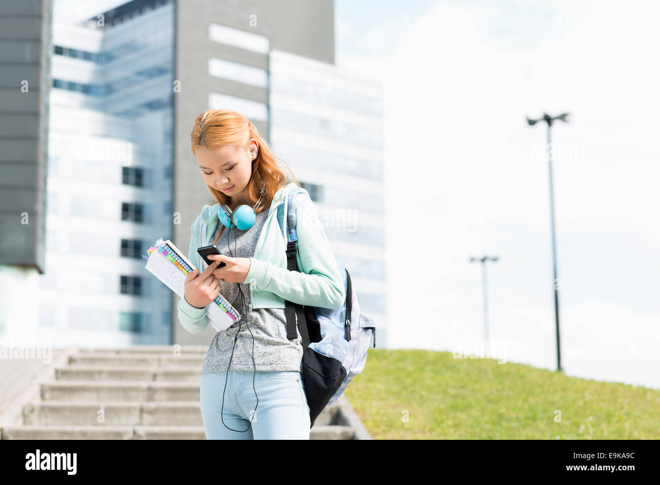 Young woman using smart phone at college campus Stock Photo
