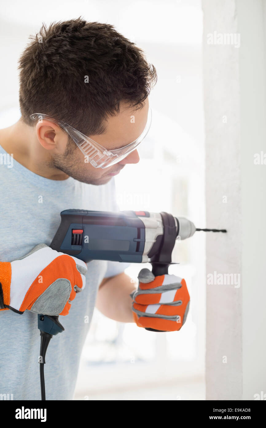 Mid-adult man drilling in wall - Stock Image