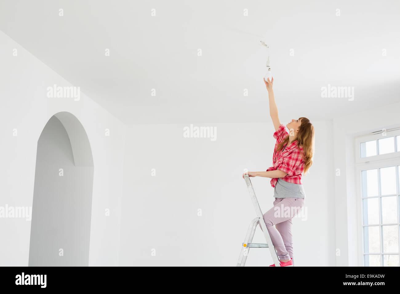 Full-length of woman on ladder fitting light bulb in new house - Stock Image