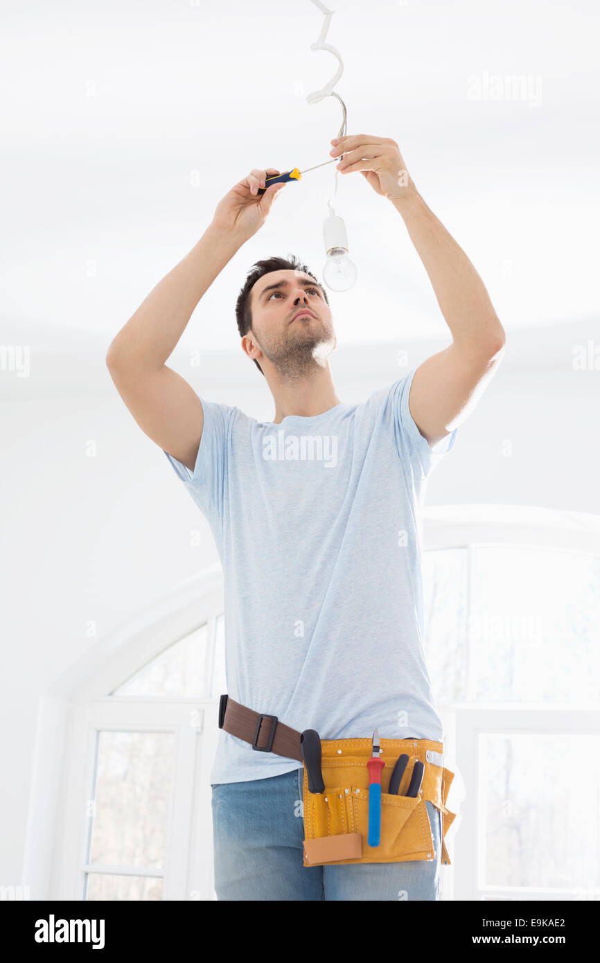 New Electrical Wiring In House Stock Photos Mid Adult Man Fixing Light Bulb Image