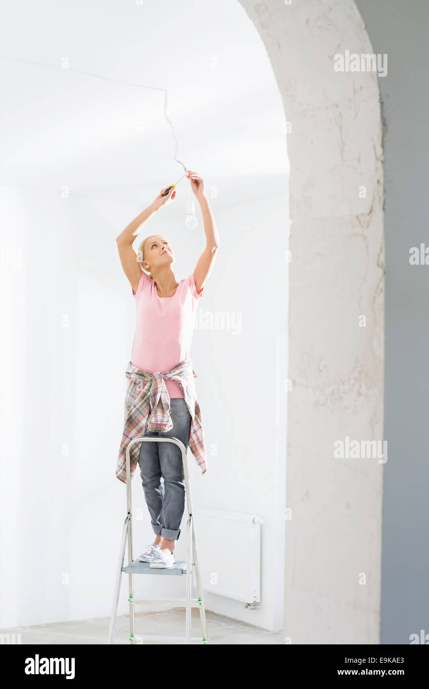 Woman on ladder fitting light bulb in new house - Stock Image