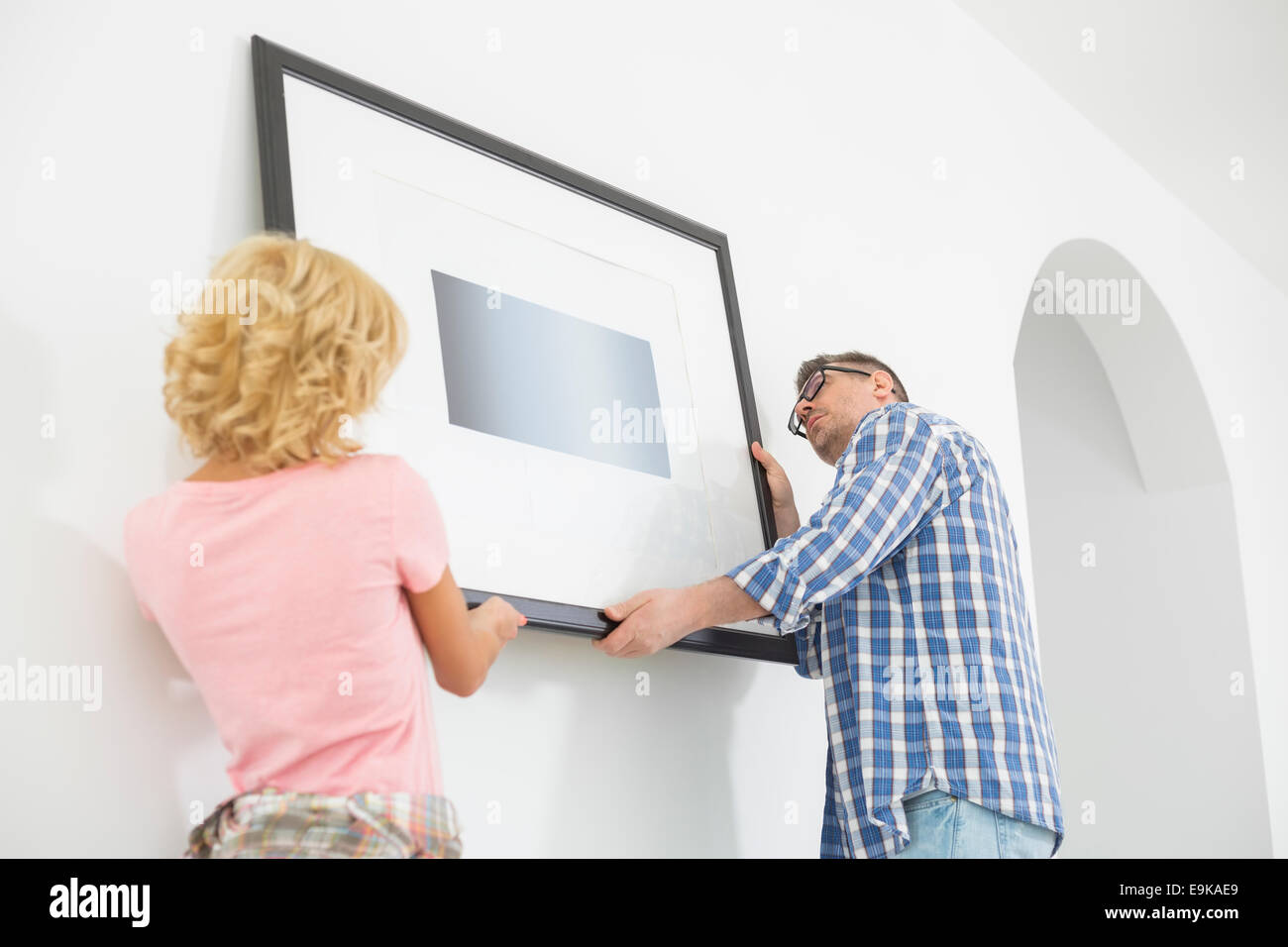 Couple hanging picture frame on wall in new house - Stock Image