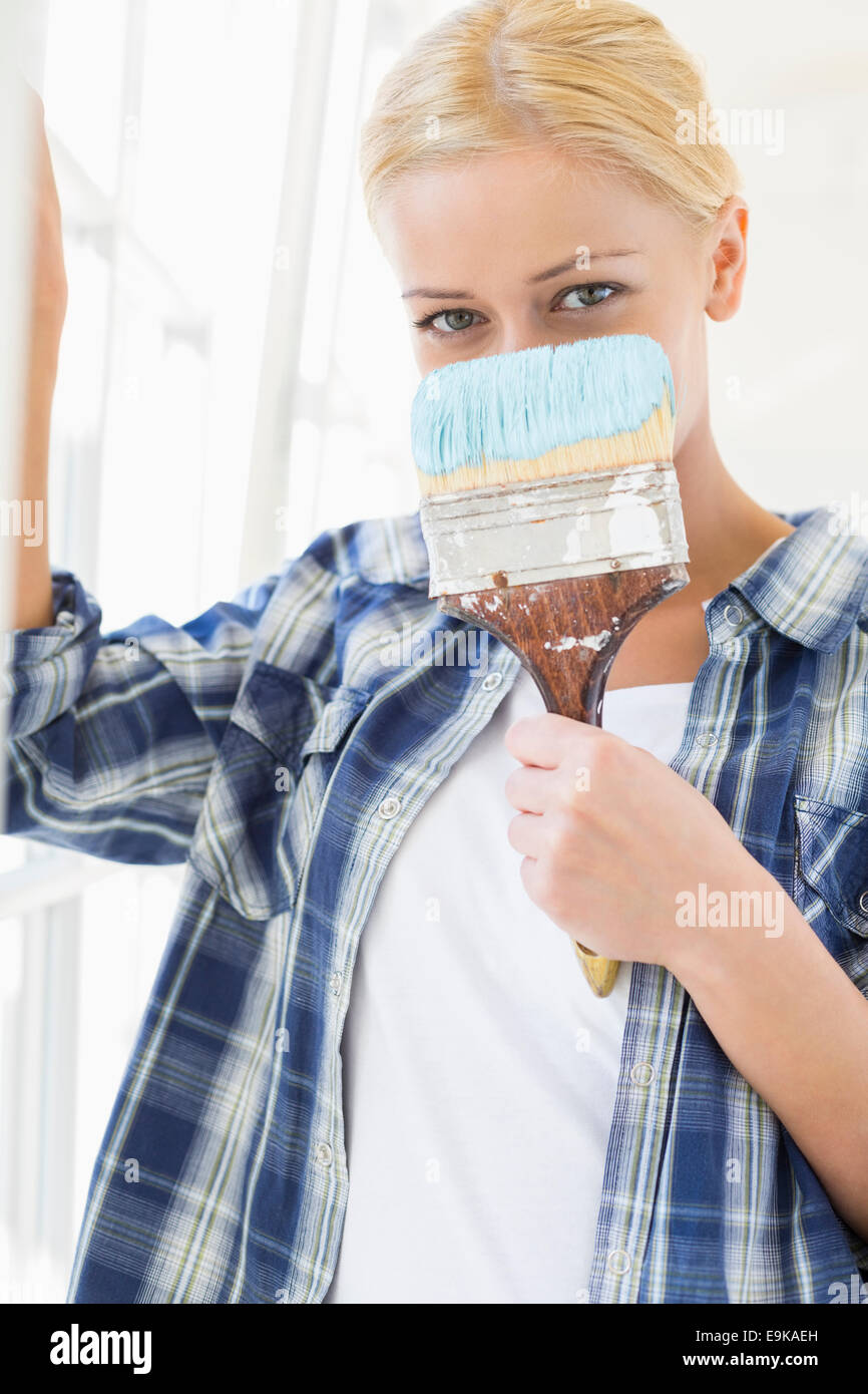 Portrait of woman holding paintbrush in front of face - Stock Image
