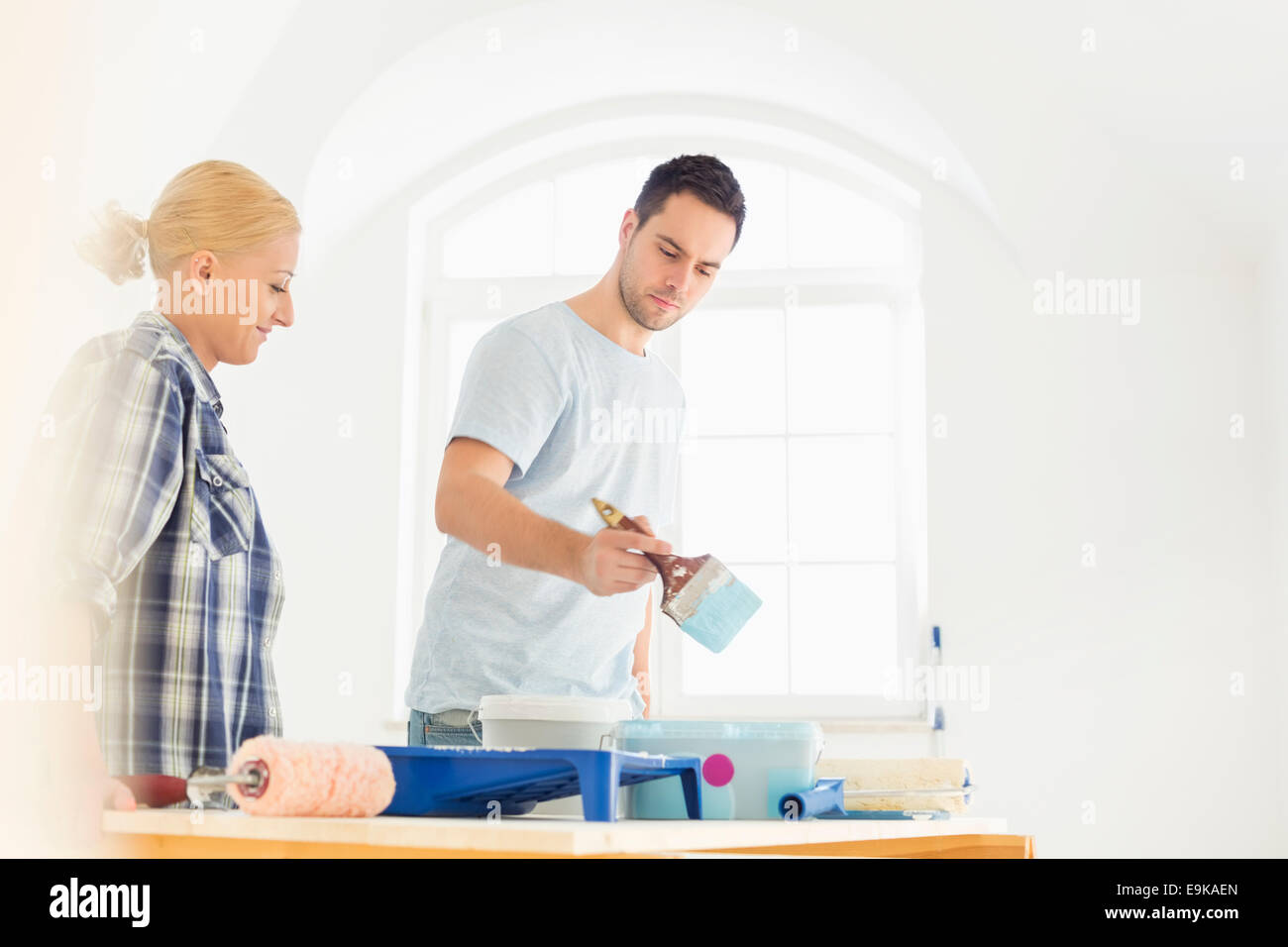 Mid-adult couple painting in new house - Stock Image