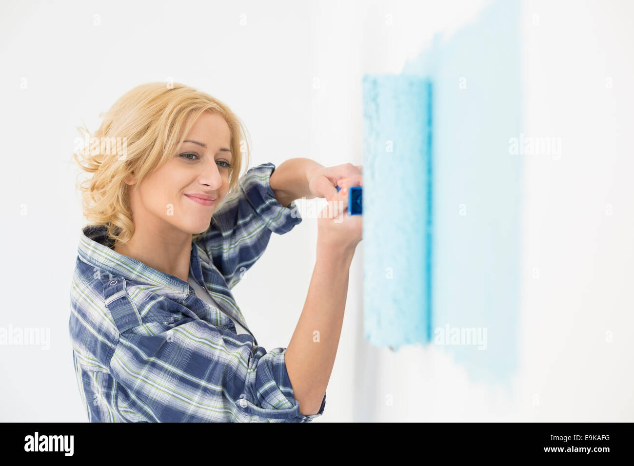 Beautiful woman painting wall with paint roller - Stock Image