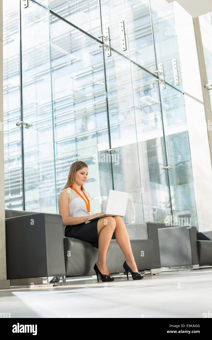 Young businesswoman using laptop at office lobby - Stock Image