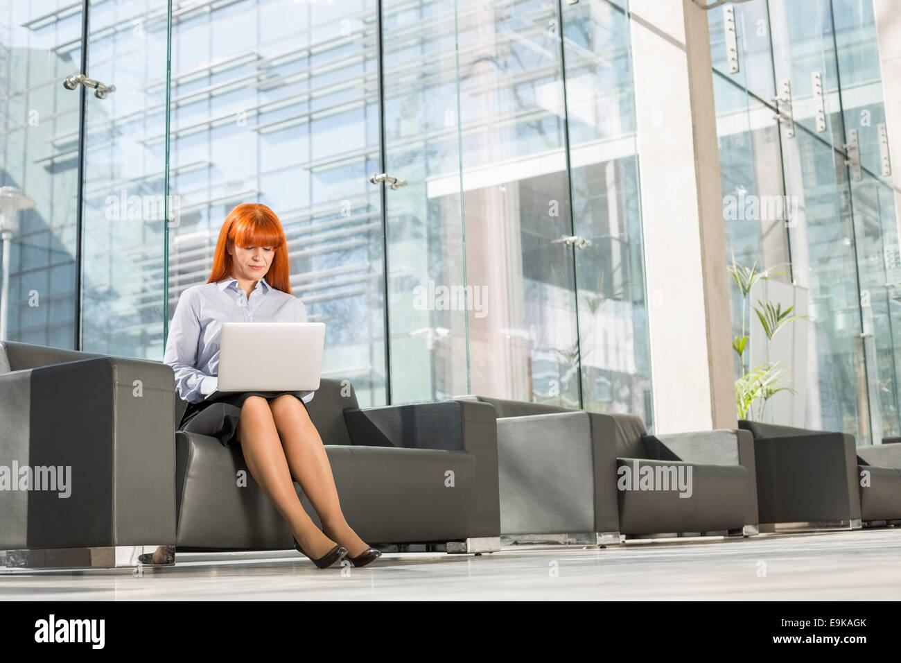 Full-length of middle-aged businesswoman using laptop at office lobby - Stock Image
