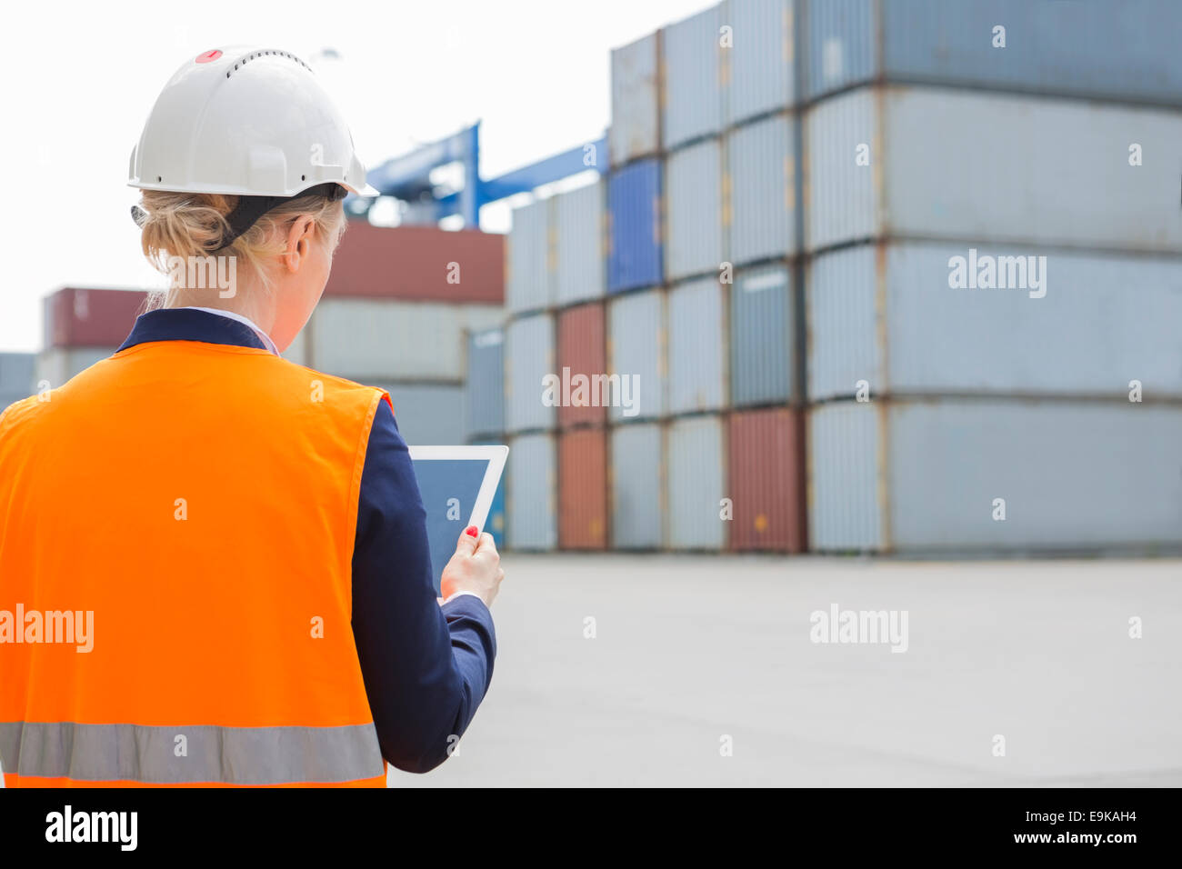 Rear view of female engineer using digital tablet in shipping yard - Stock Image