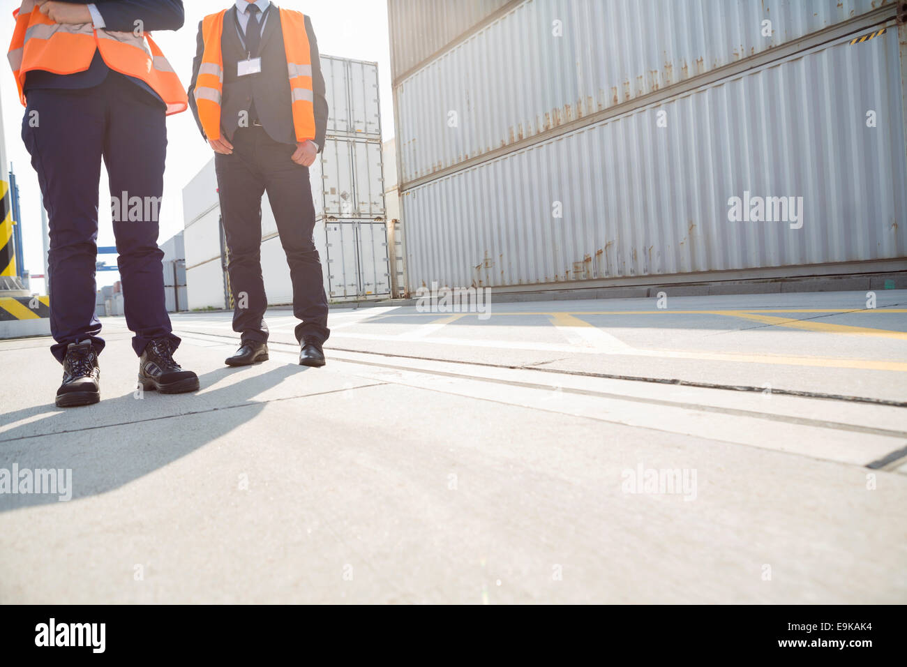 Low section of workers standing in shipping yard - Stock Image