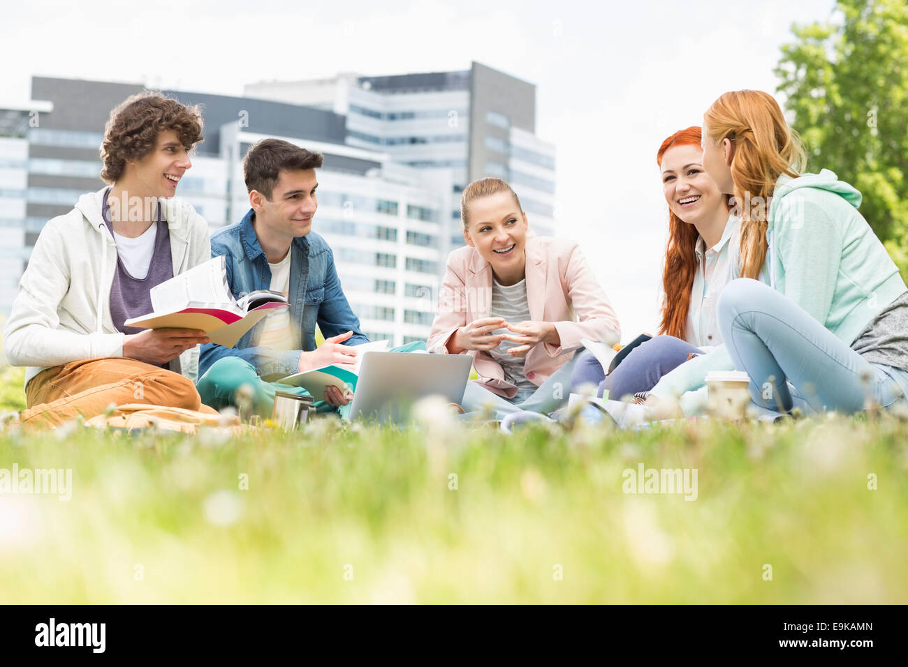 University students studying together on grass - Stock Image