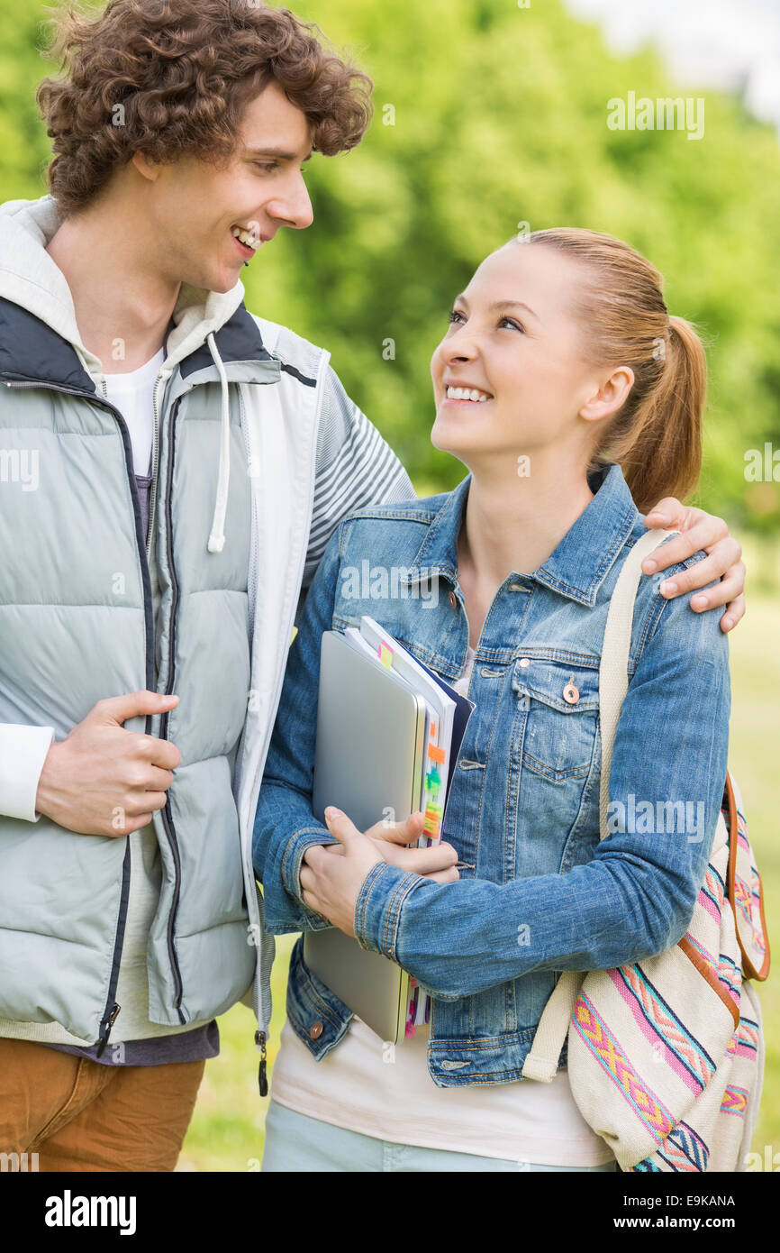 Happy college students looking at each other at campus - Stock Image