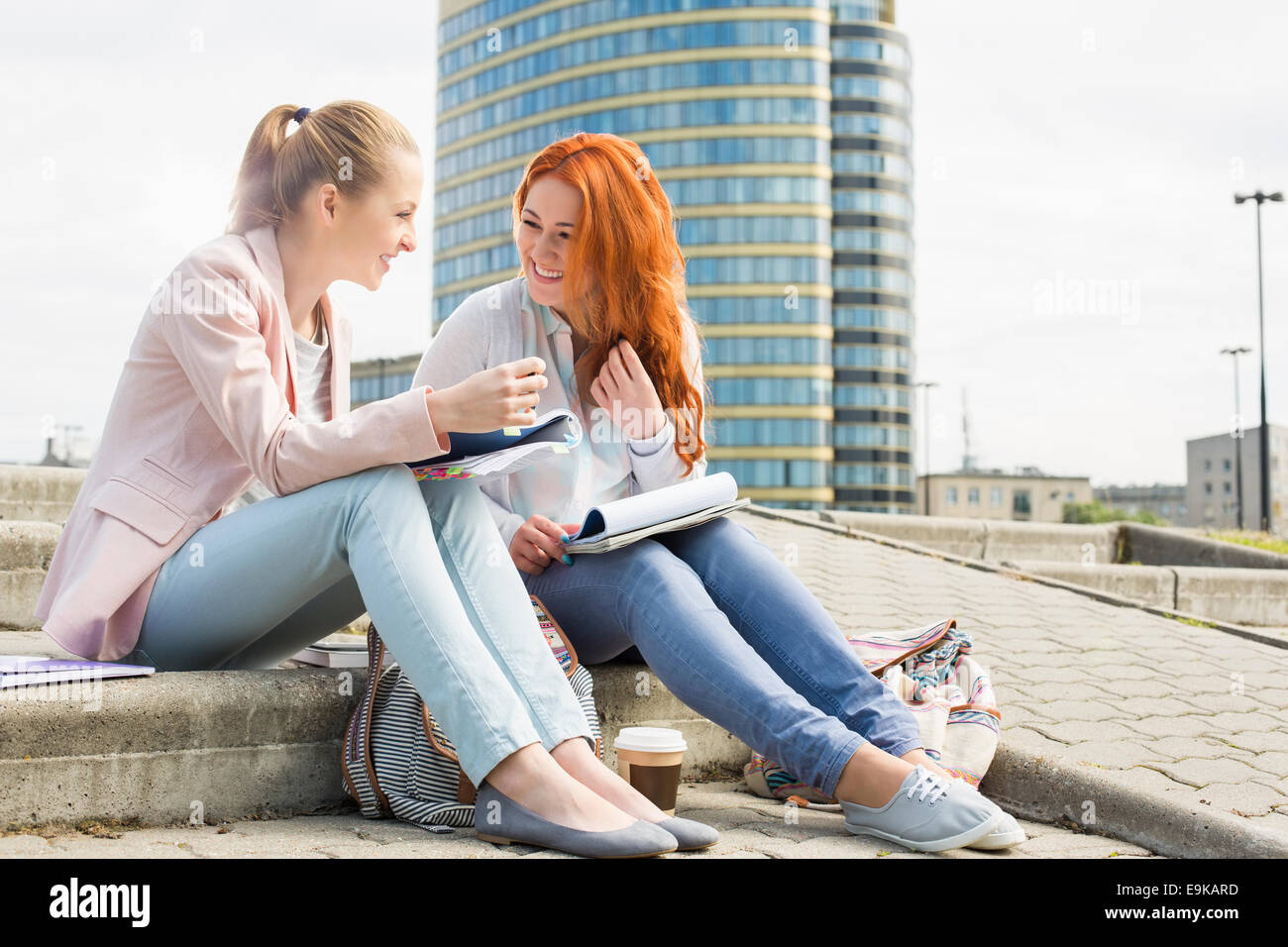 Full length of smiling female college students studying on steps against building - Stock Image