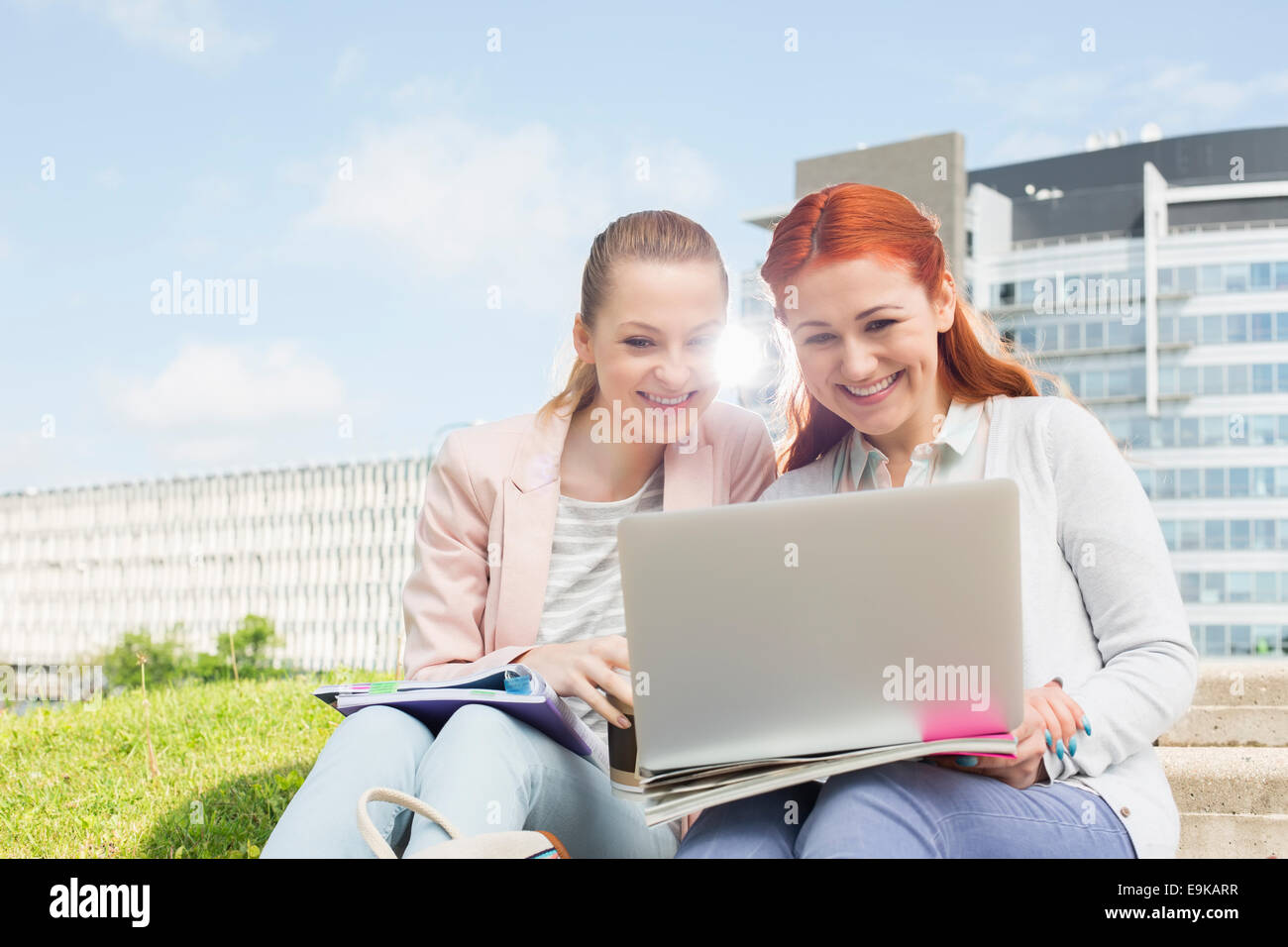 Smiling young university students using laptop with buildings in background - Stock Image