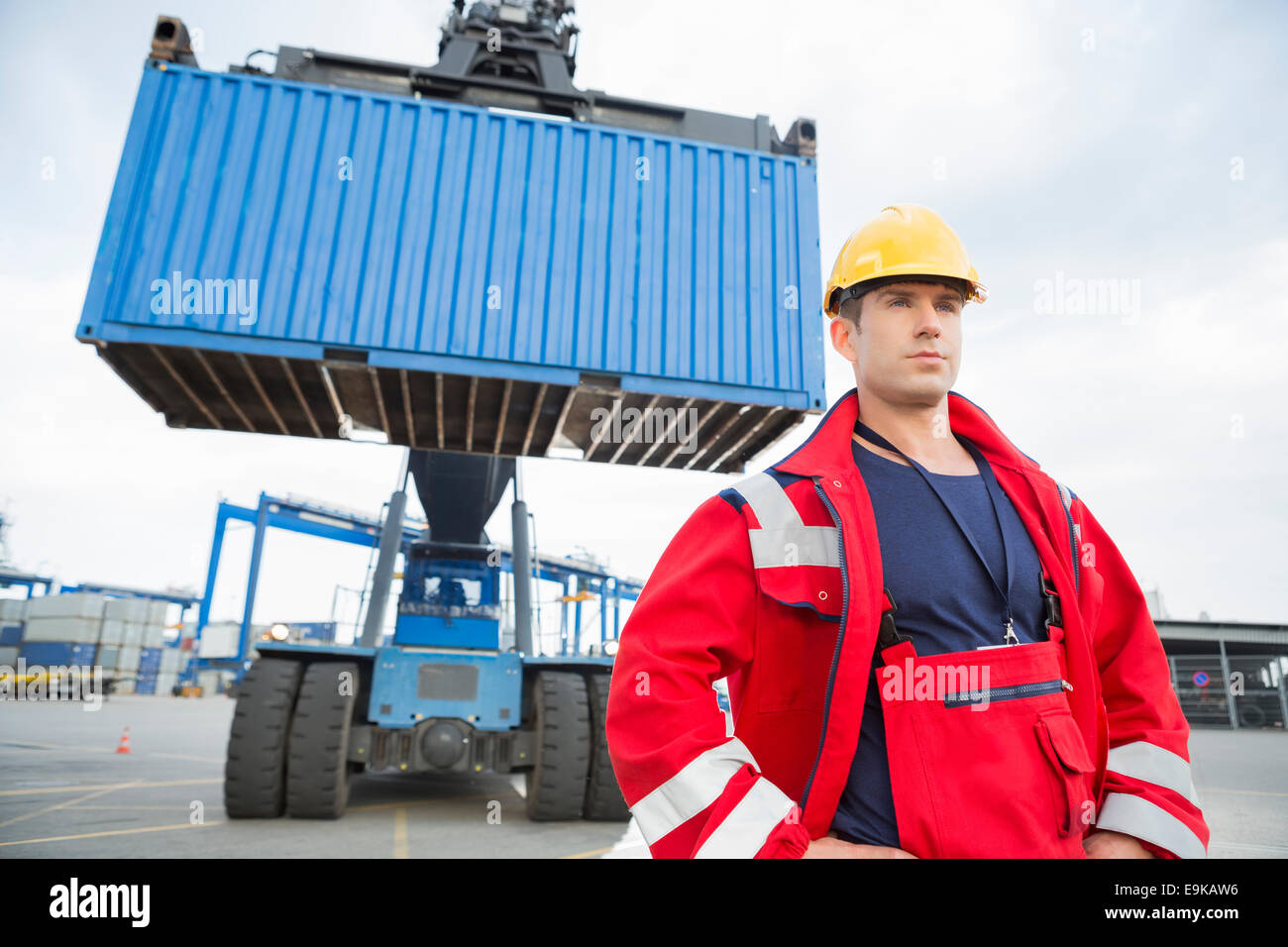 Confident male worker standing in front of freight vehicle at shipyard - Stock Image