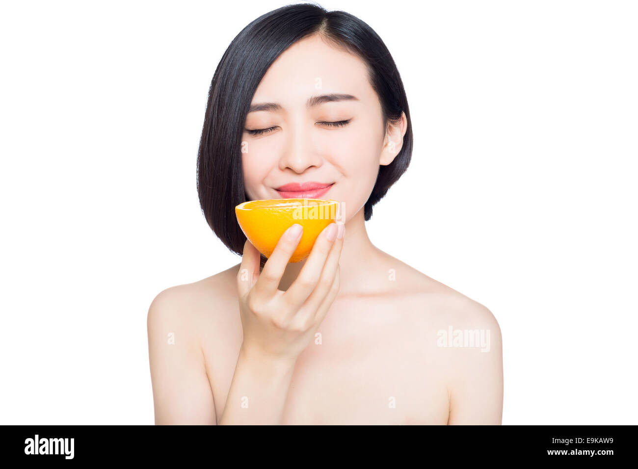 young woman with oranges in her hands, white background - Stock Image