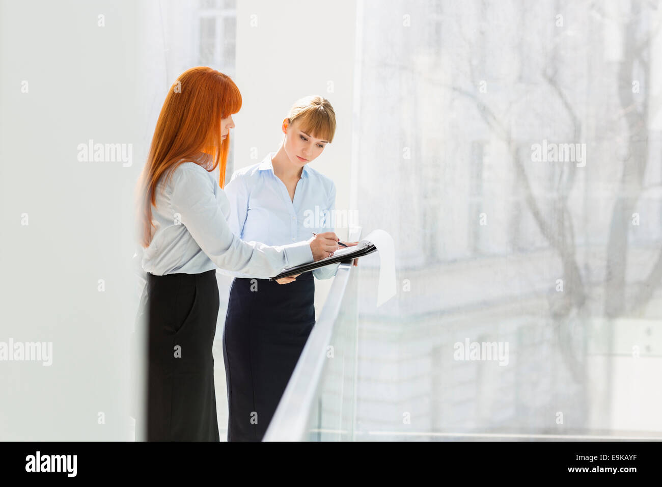 Businesswomen doing paperwork while standing by railing in office - Stock Image