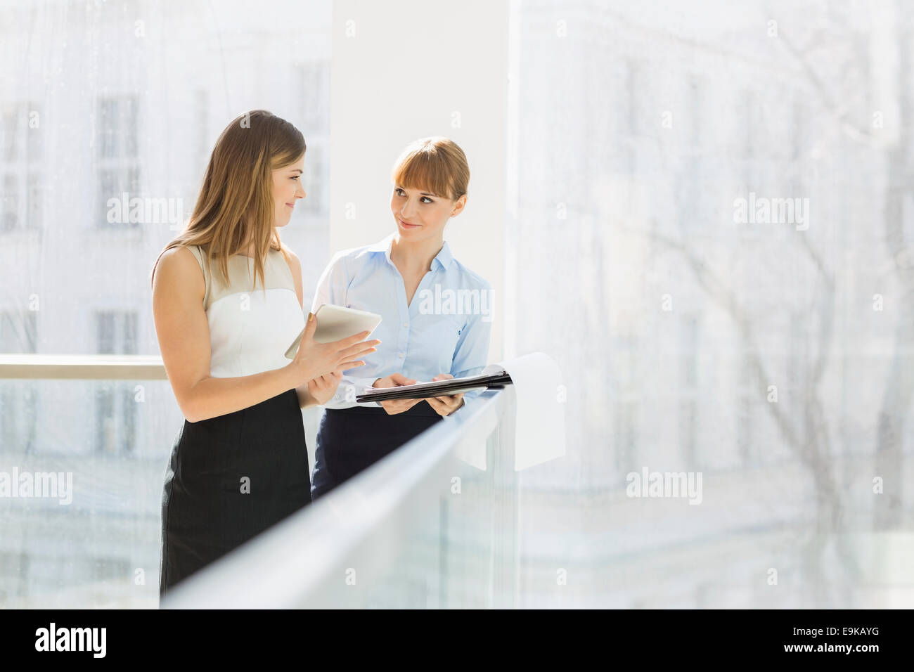 Businesswomen discussing over tablet PC while standing by railing in office - Stock Image
