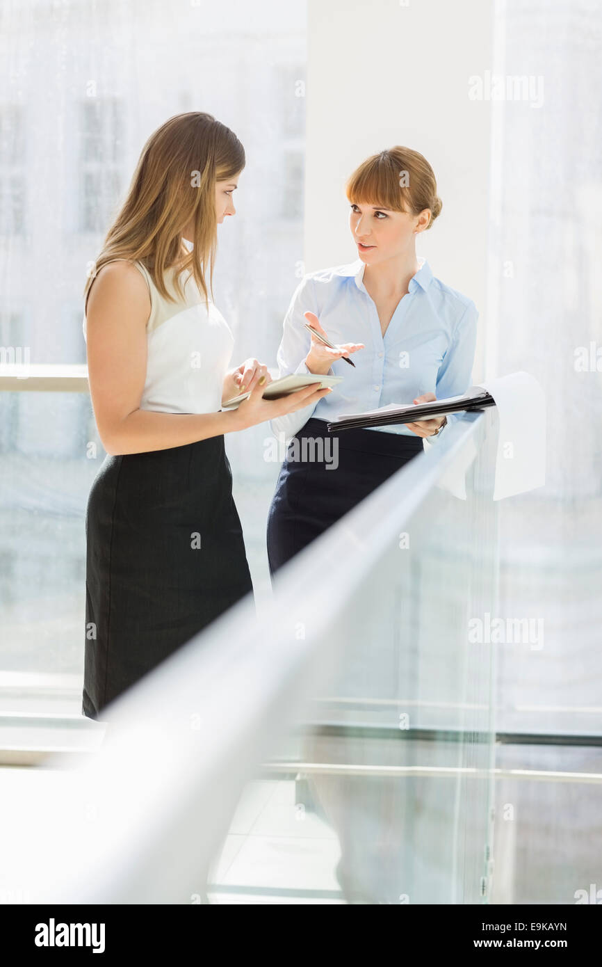 Businesswomen discussing while standing by railing in office - Stock Image