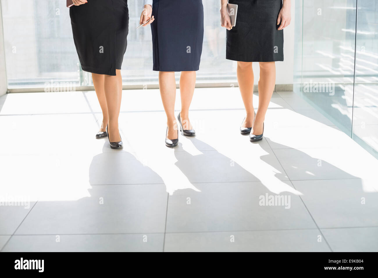 Low section of businesswomen standing on tiled floor in office - Stock Image