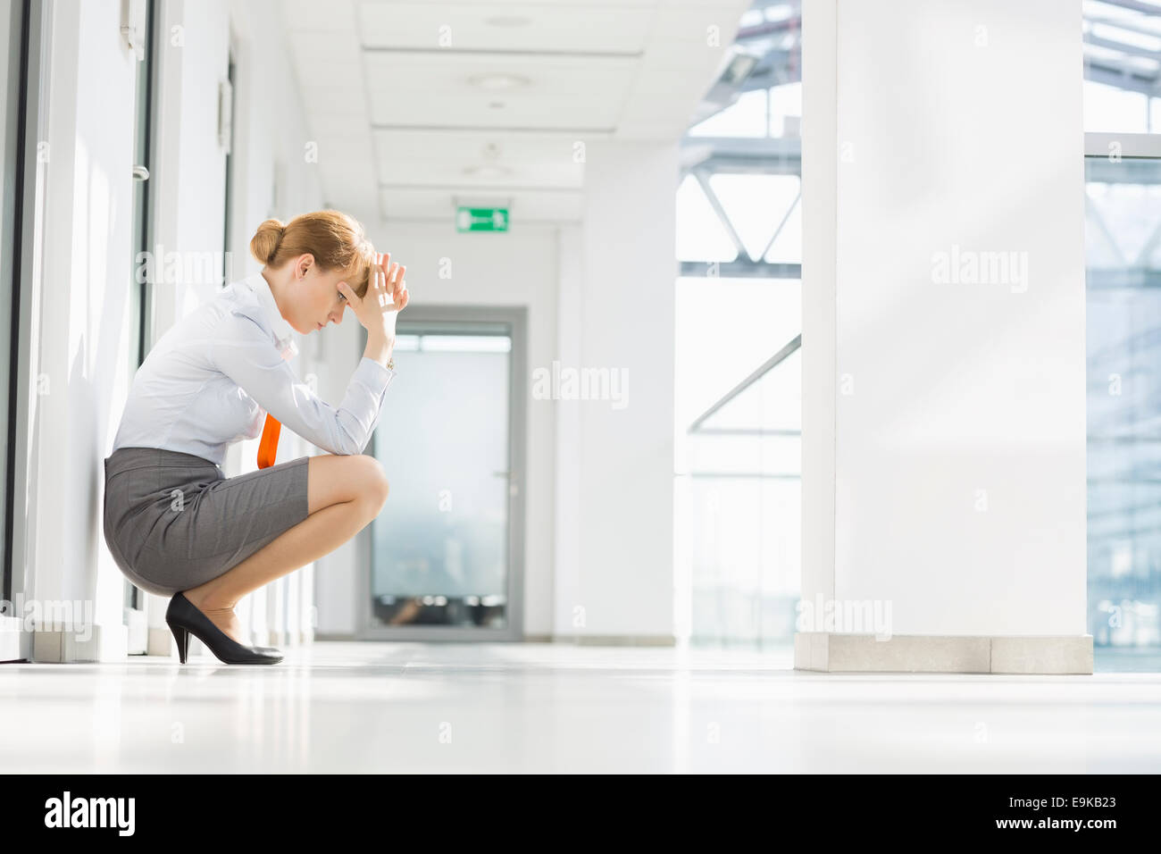 Full-length side view of stressed businesswoman crouching at office hallway - Stock Image