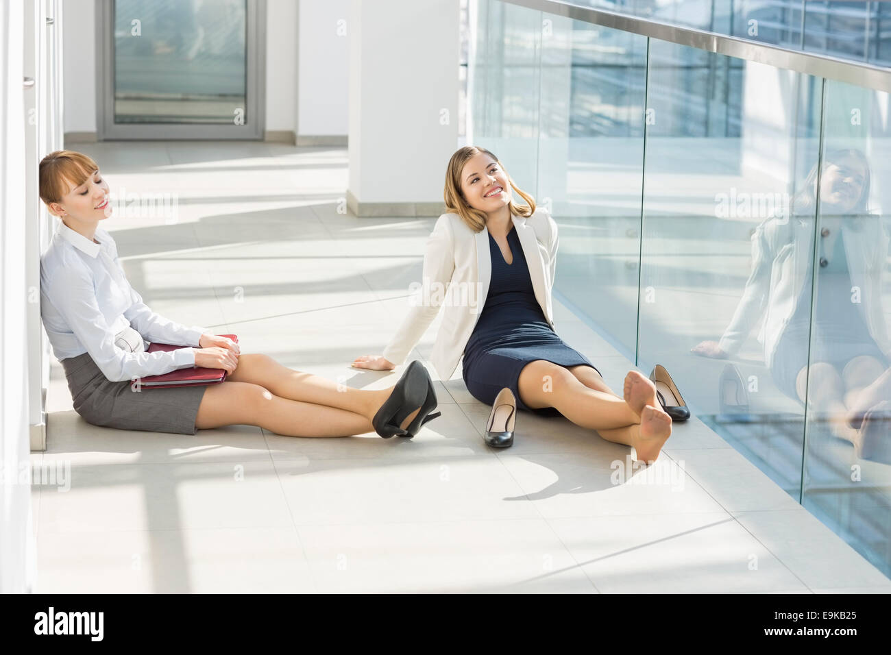 Tired businesswoman relaxing at office hallway - Stock Image