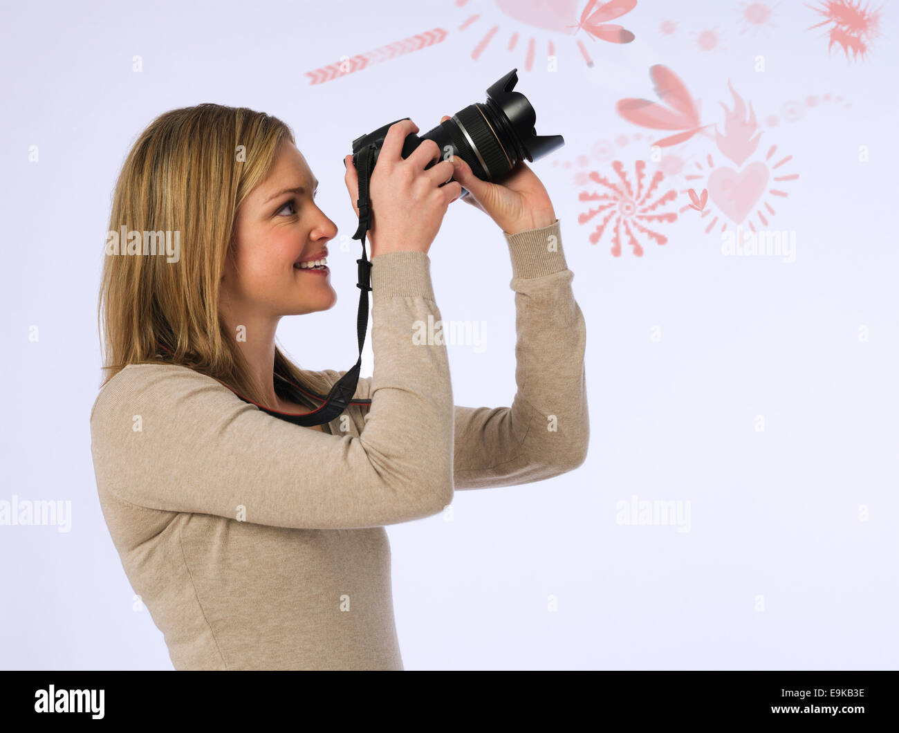 Side view of young woman photographing various patters over white background - Stock Image