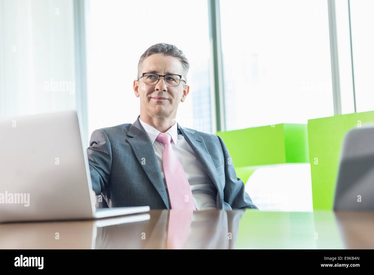 Middle-aged businessman with laptop sitting at conference table - Stock Image