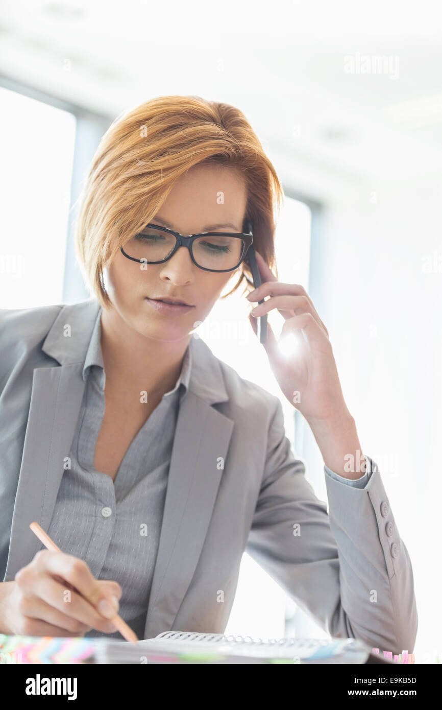 Young businesswoman on call while writing at desk in office - Stock Image