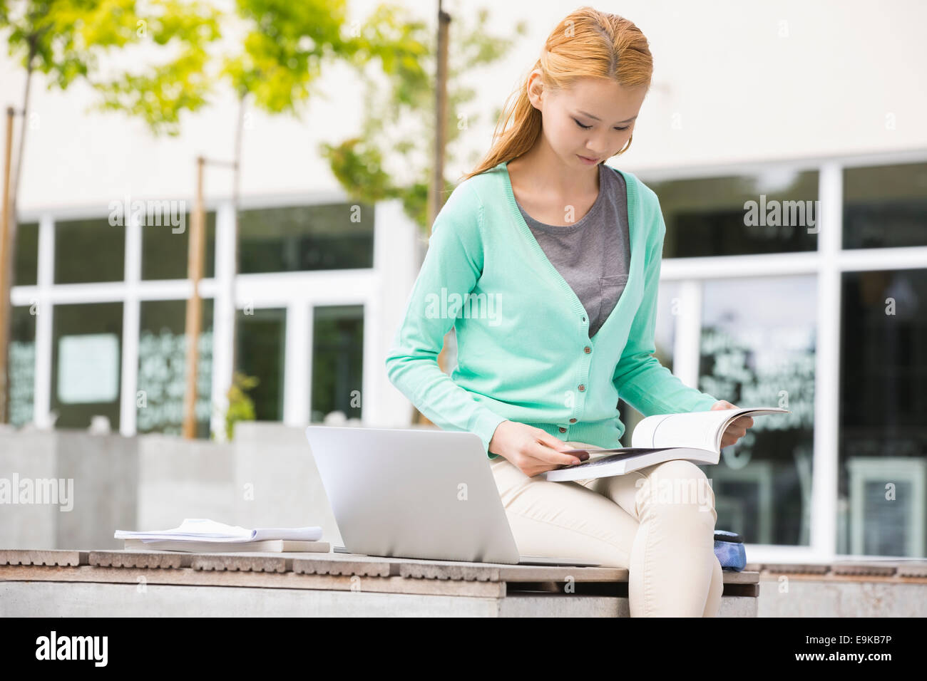Young woman reading book at college campus - Stock Image