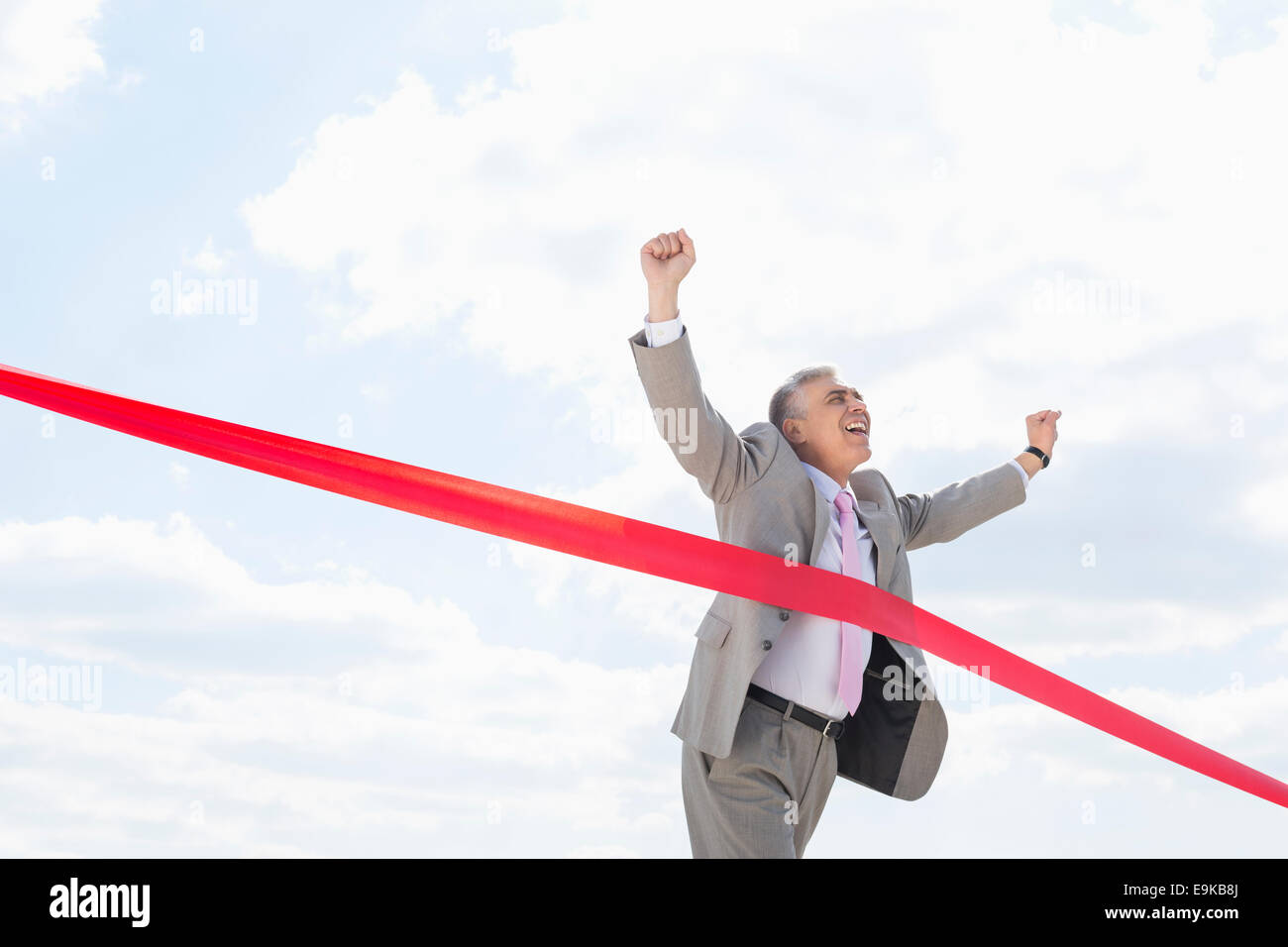 Cheerful businessman crossing finish line against sky - Stock Image