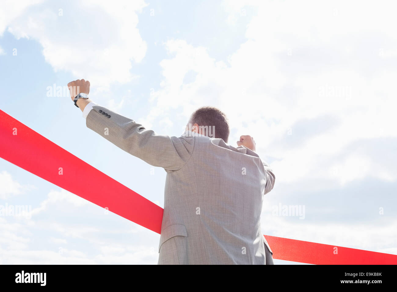 Rear view of businessman crossing finish line against sky - Stock Image
