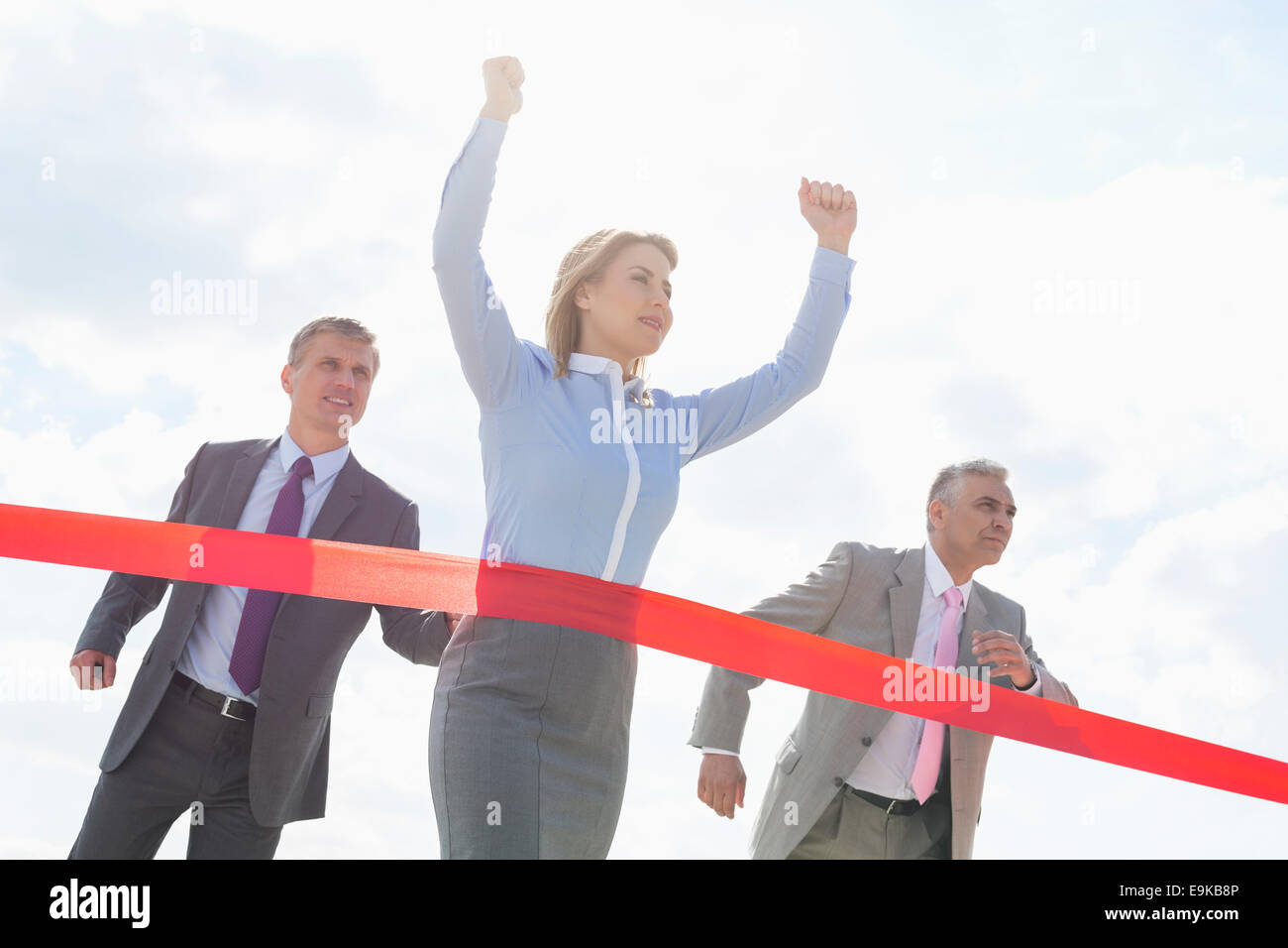 Businesswoman crossing finishing line with colleagues in background - Stock Image