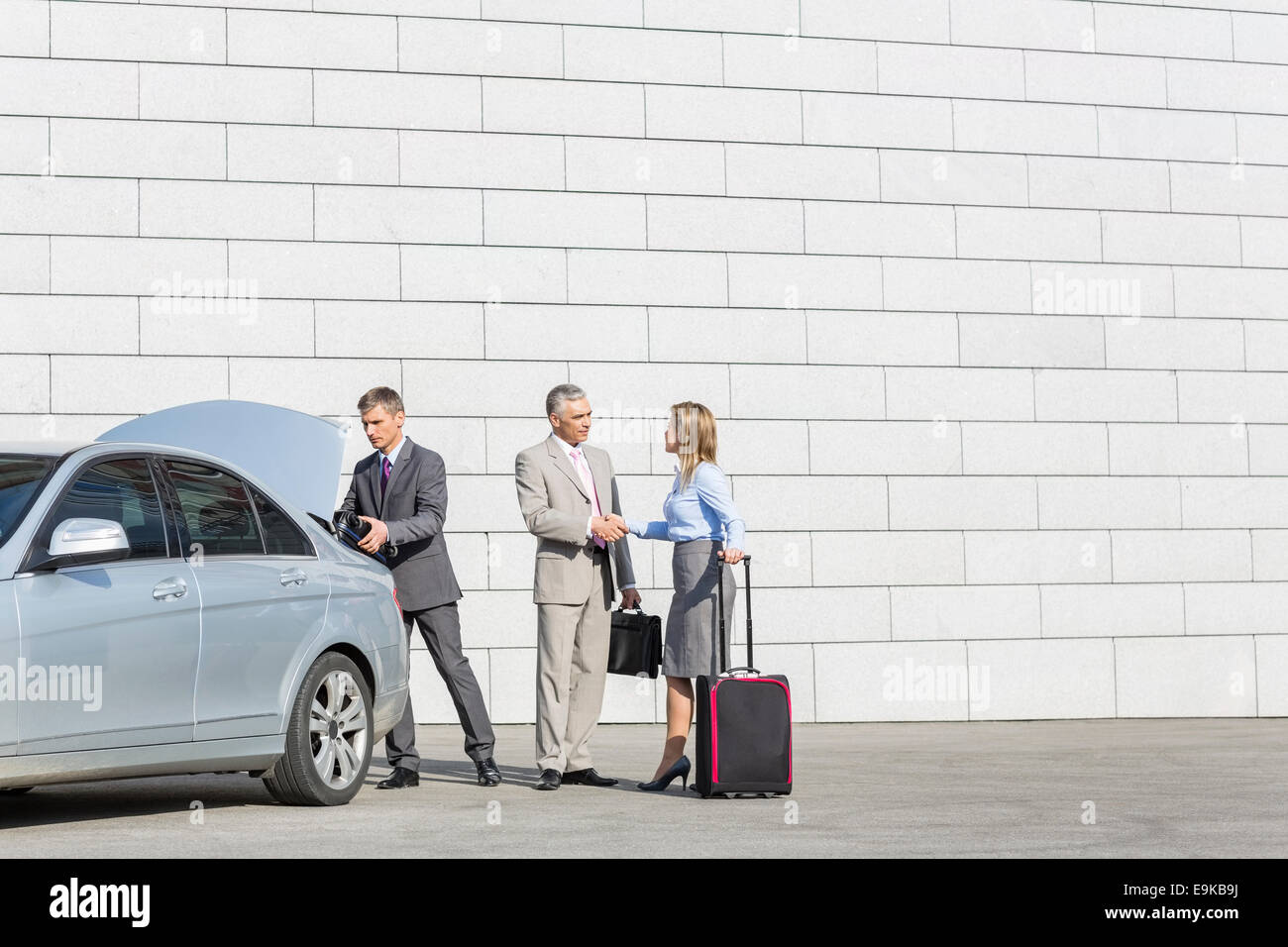 Businesspeople with luggage shaking hands outside car on street - Stock Image