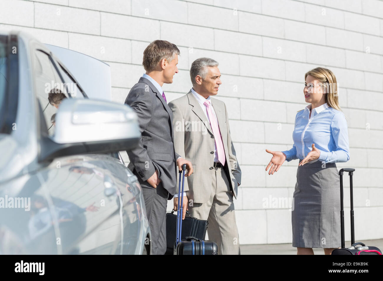 Businesspeople with luggage discussing outside car Stock Photo