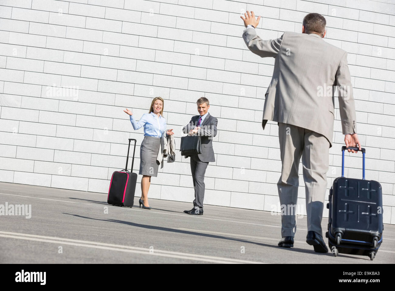 Rear view of businessman carrying luggage waving hand to colleagues - Stock Image