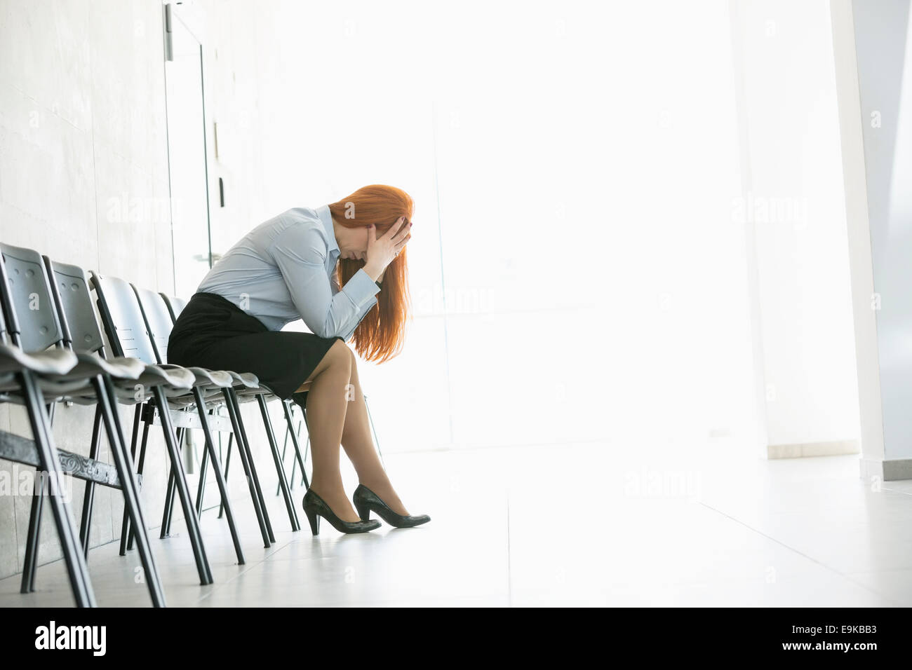 Side view of exhausted businesswoman sitting on chair in office - Stock Image