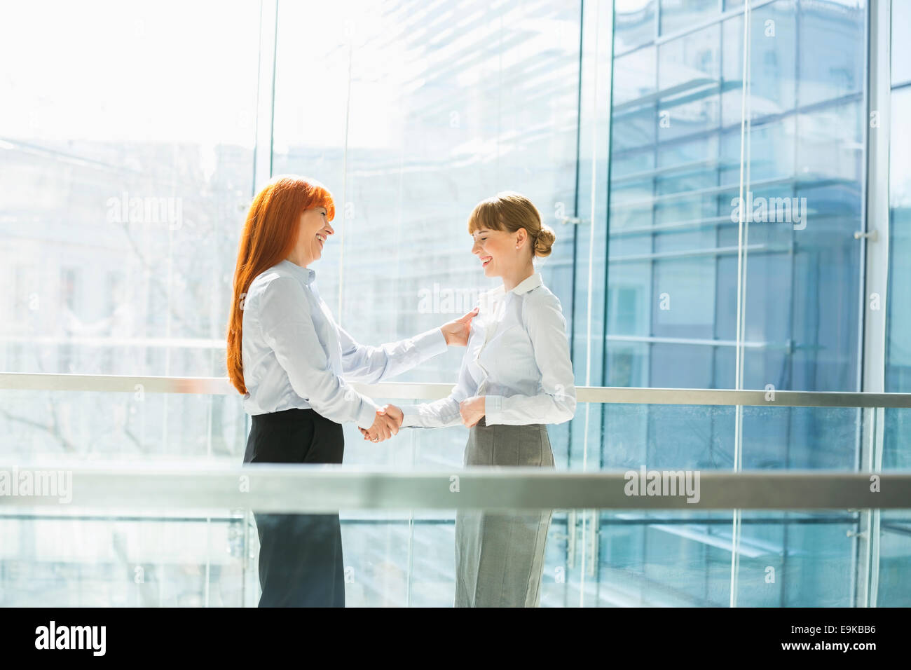 Happy businesswomen shaking hands in office - Stock Image