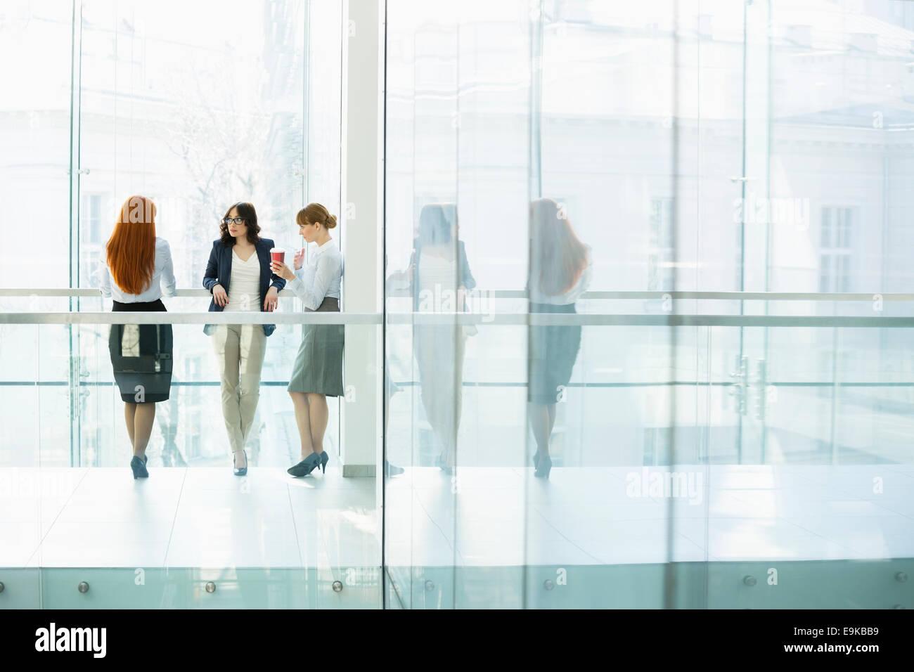 Businesswomen conversing at office hallway - Stock Image