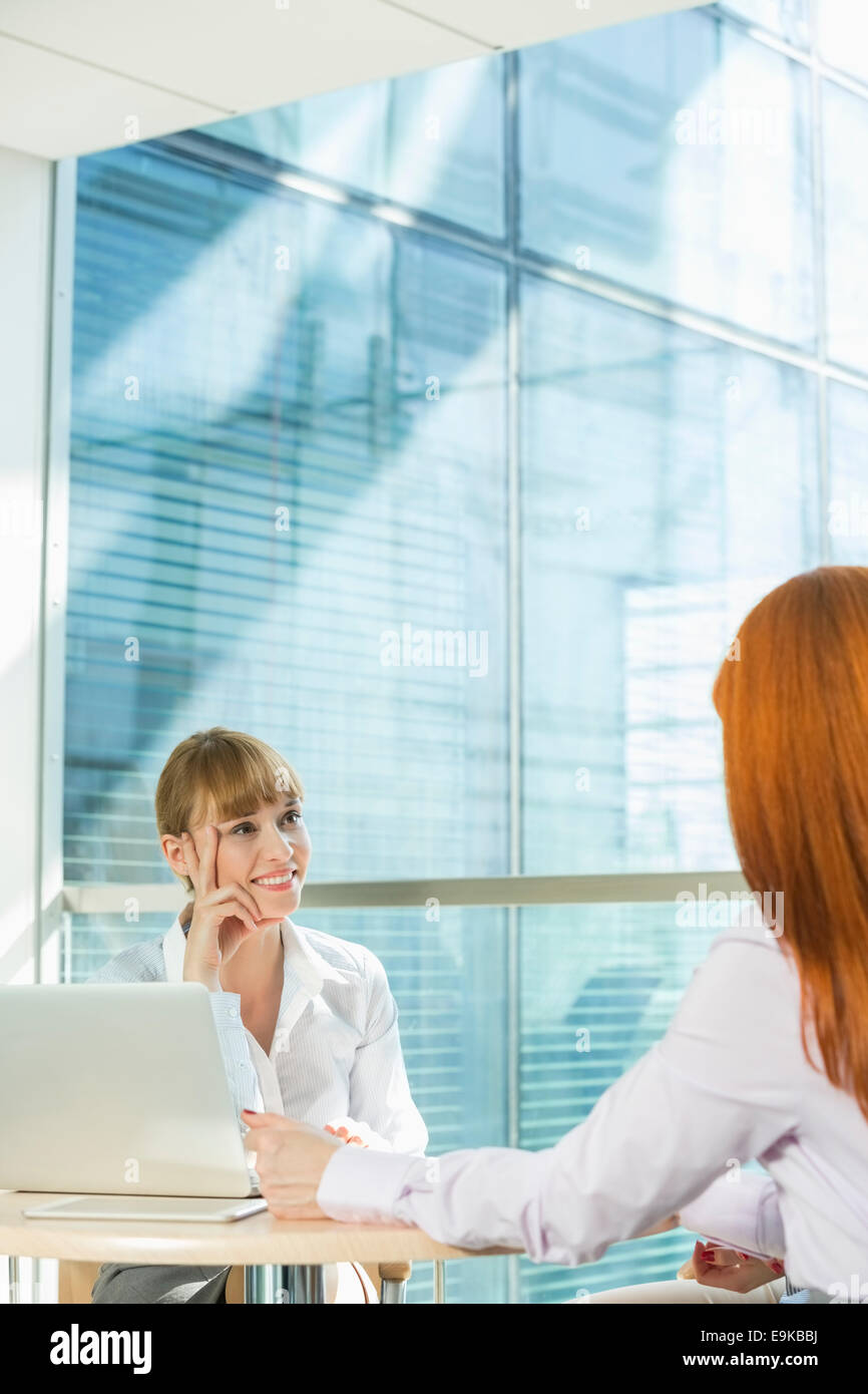 Businesswomen discussing at table in office - Stock Image