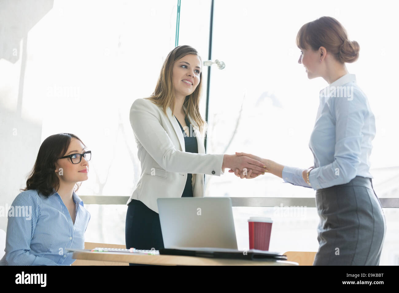 High angle view of businesswomen shaking hands at table in office - Stock Image