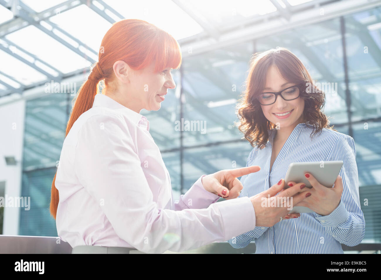 Businesswoman showing something on tablet PC to colleague in office Stock Photo