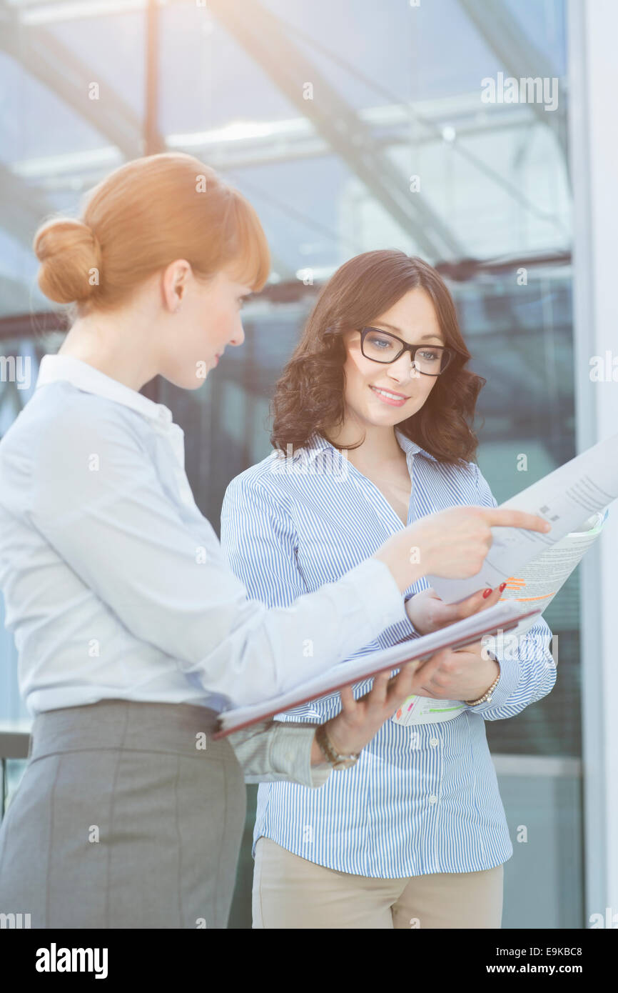 Businesswoman showing document to colleague in office - Stock Image
