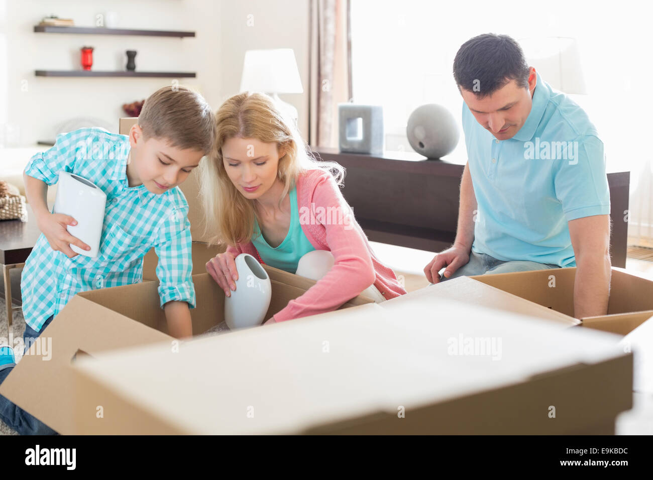 Family unpacking cardboard boxes in new house - Stock Image