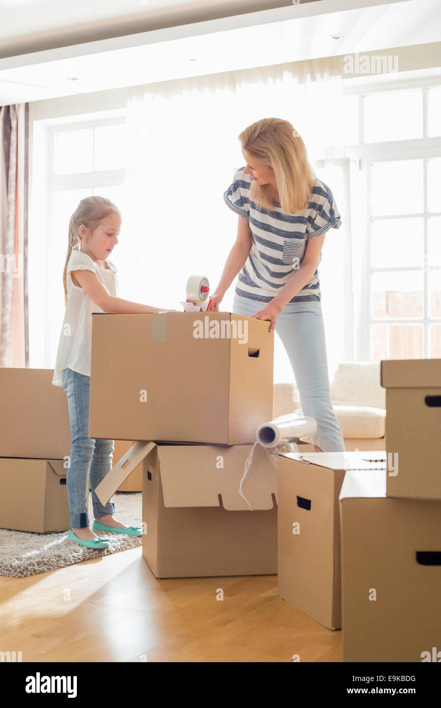 Mother and daughter packing cardboard boxes at home - Stock Image