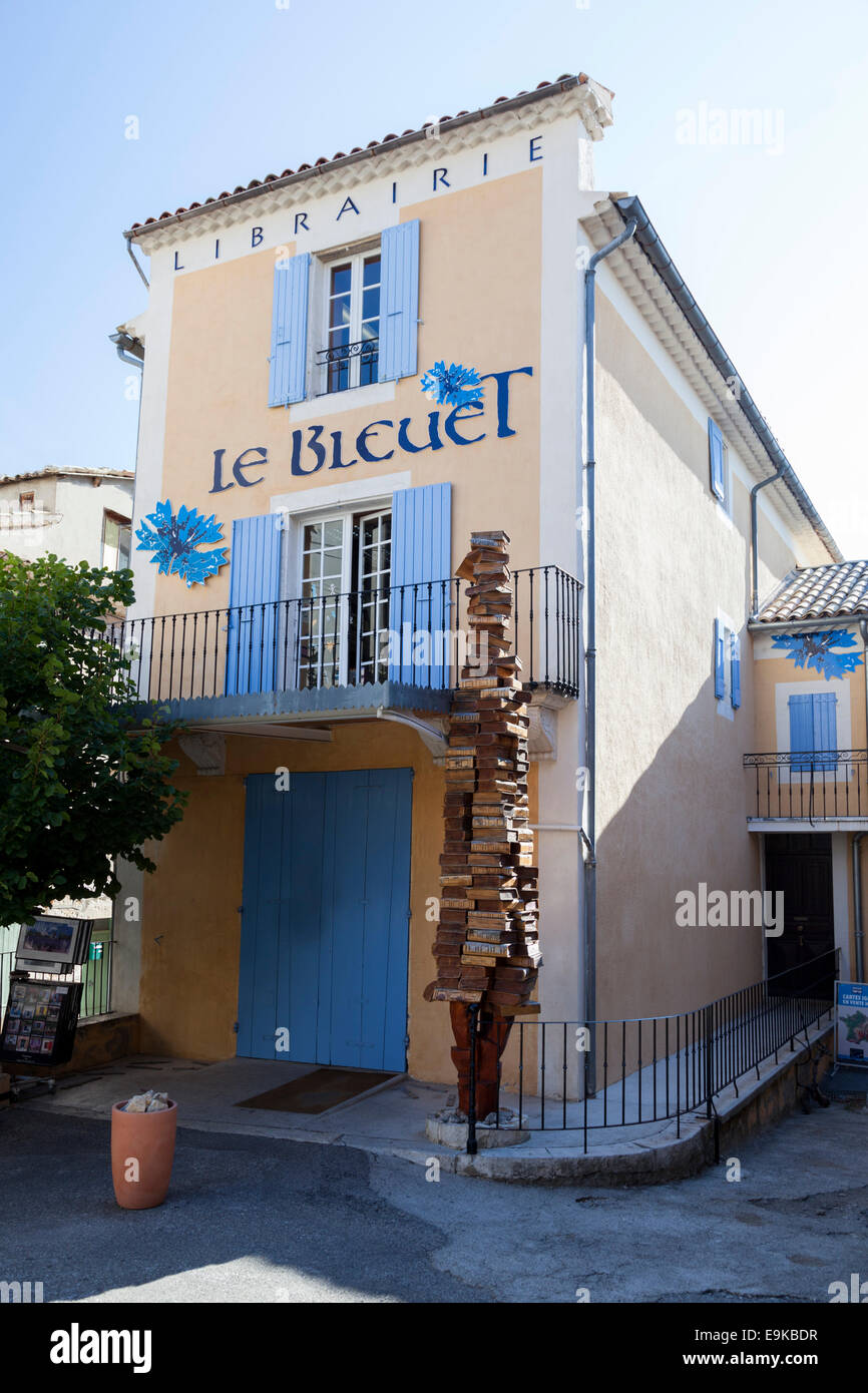"""A stack of books as a sign, in front of """"the Cornflower"""" bookshop entrance, in Banon (France). Librairie les """"Bleuets"""", Stock Photo"""