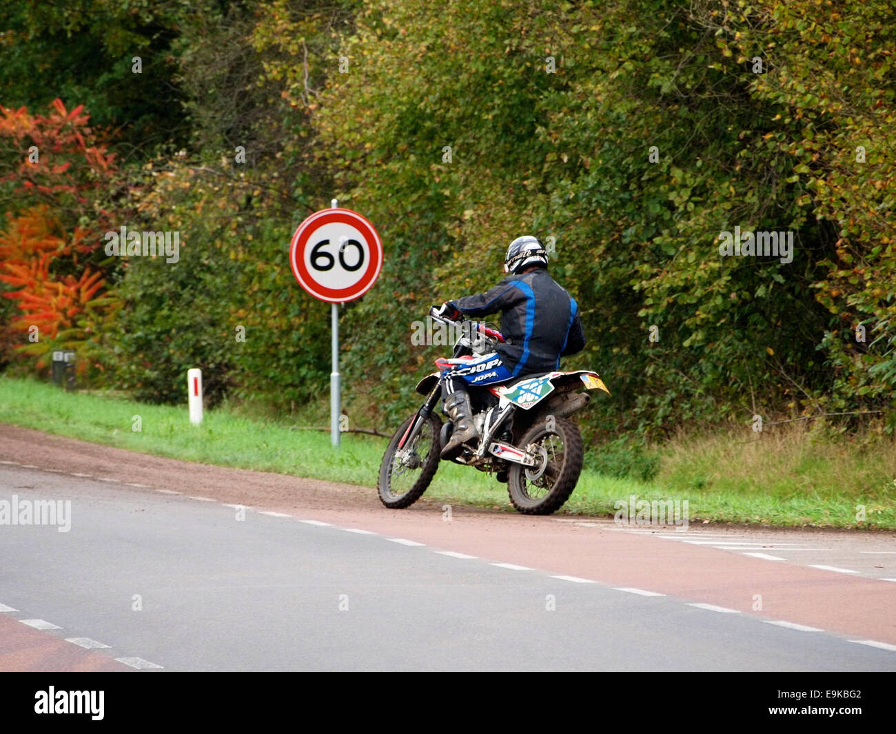 Man on Husqvarna offroad motorcycle passing 60 kmh speed limit sign in Ruurlo, the Netherlands - Stock Image