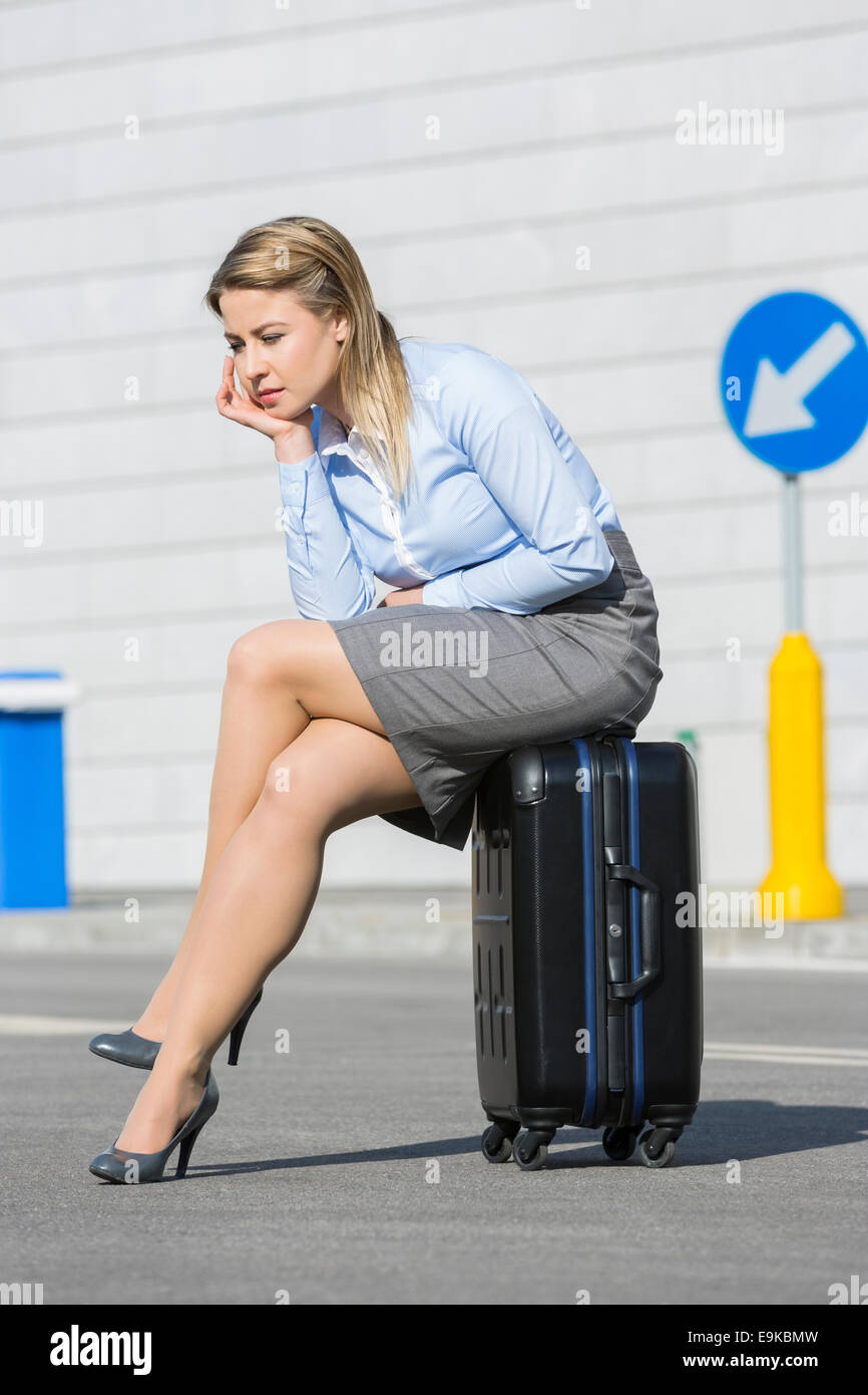 Full length of exhausted businesswoman sitting on luggage - Stock Image
