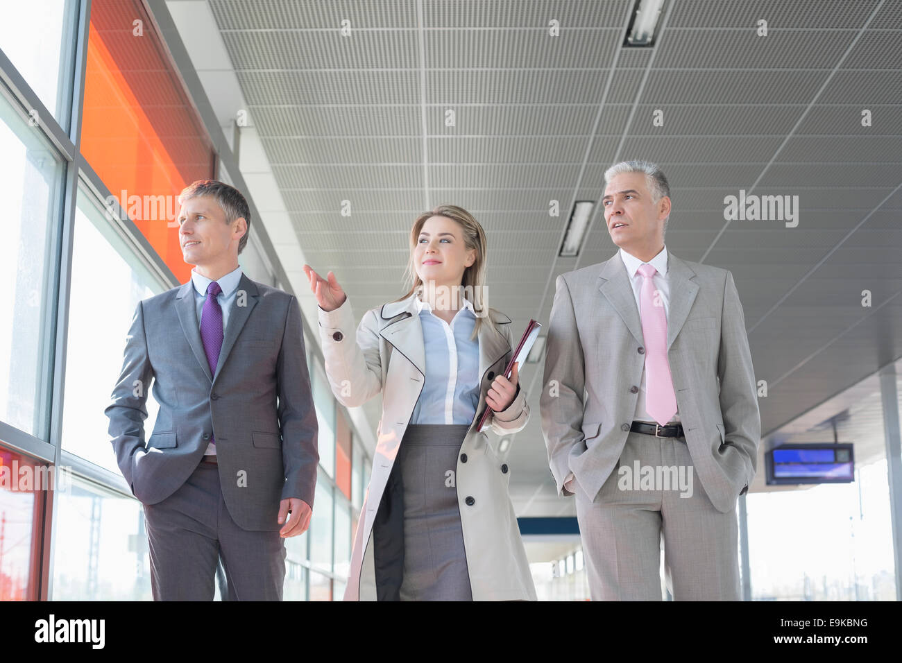 Business people discussing while walking on train platform - Stock Image