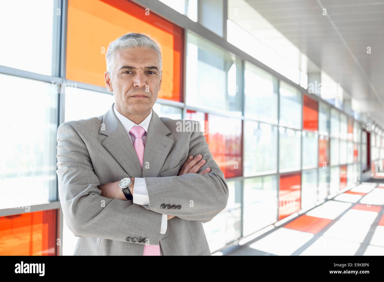 Portrait of confident middle aged businessman at railroad station - Stock Image